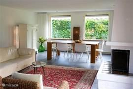 Overzicht van de sfeervolle, ruime huiskamer, met leren bankstel van Molinari, open haard en een robuuste eettafel. Wifi, muziekinstallatie en internet-tv.