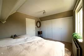 Grote slaapkamer die we ook wel de boomkamer noemen omdat het bed gemaakt is van zwaar Frans eiken, door een kunstenaar. Voorzien van kwaliteitsmatrassen en hangkasten.