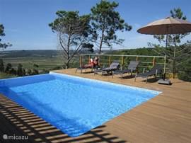 Het verwarmde zwembad met ligzetels en prachtig uitzicht