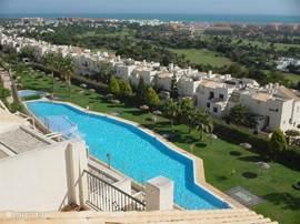 Het grote zwembad van de woonwijk La Ladera del Golf en het mooie uitzicht vanaf deze woonwijk.