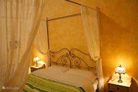 Ruime moderne slaapkamer met hemelbed en zitgelegenheid