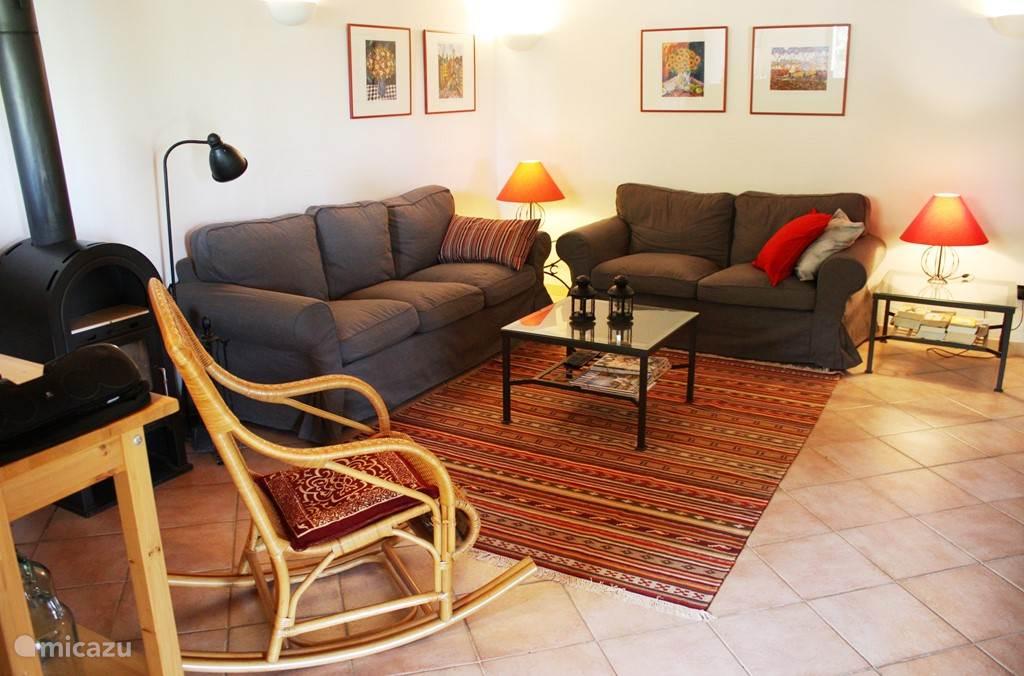 De woonkamer incl. tweezits- en driezitsbank, schommelstoel en houtkachel.