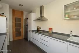 De ruime keuken beschikt over alle faciliteiten om heerlijk te kokkerellen.
