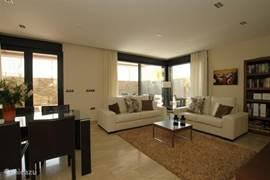 De royale woon-/eetkamer is comfortabel en licht, met ramen en openslaande deuren die toegang geven tot de terassen en het zwembad.