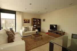 De woonkamer is comfortabel ingericht en biedt veel mogelijkheden voor ontspanning.