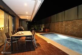Het zwembad met romeinse trappen en verlichting geeft 's avonds een romantisch beeld.