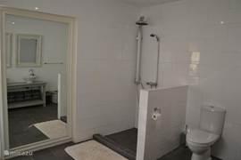 Master-badkamer met inloop regendouche en dubbele wastafel.