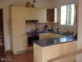 De open keuken in U vorm,in provencaalse kleuren.