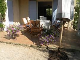 De tuintafel met stoelen op het terras