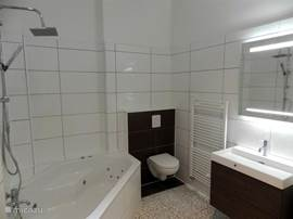 Spacious bathroom with 2-person Jacuzzi tub, rain shower and hand shower, large sink, hair dryer, and marble floor with underfloor heating.