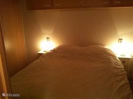 De gezellige slaapkamer met grote schuifdeurkast en legkasten