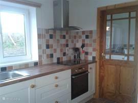 Keuken met deur naar de bijkeuken. In de bijkeuken bevinden zich wasmachine en droger, magnetron en de 'hotpress'.