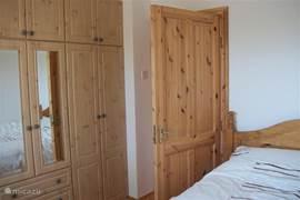 Slaapkamer met tweepersoons bed en veel opbergruimte.