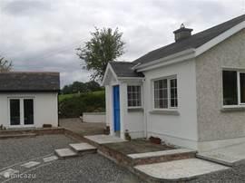 Voorzijde van cottage met blauwe 'stable door' (bovenhelft kan apart opengezet worden). Ook zichtbaar is de tot studio gerenoveerde schuur die gebruikt kan worden voor opslag van tuinstoelen, golftassen, fietsen, kayaks etc.