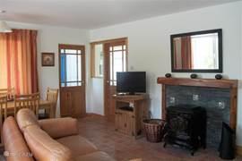 Eet/woonkamer met houtkachel en (verschuifbare) bank. Tevens twee stoelen aanwezig (niet zichtbaar).