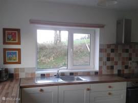 Moderne keuken met veel licht. Bevat o.a. waterkoker, afwasmachine, keramische plaat, oven, koelkast, vriezer, opbergkast.