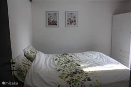 Slaapkamer 2 met twee-persoons bed (160x200) met een deur naar het terras waar in de ochtend de zon naar binnen lacht. de slaapkamer heeft aan de buitenkant van de deur naar het terras 2 zware, openslaande luiken die de kamer, indien gewenst, in een donkerkamer kunnen omtoveren.