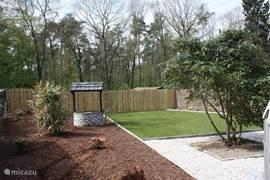 Uitzicht op de achtertuin vanuit het achterste terras aan de zijkant van het huis. Op de achtergrond ziet u het begin van het bos. De tuin is zeer netjes onderhouden maar biedt tegelijk voldoende ruimte voor kinderen en/of honden om te spelen.