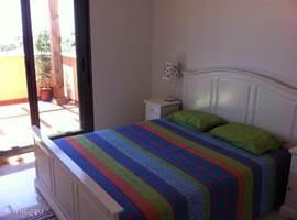 1e slaapkamer met groot dubbelbed. Inbouwkasten van groot volume met een schuifdeur naar het terras