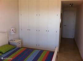 Slaapkamer met dubbelbed en grote opbergkasten