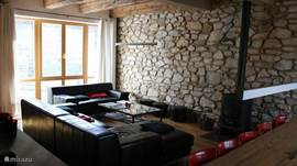 Ruime gezellige woonkamer met houtkachel en originele muur.
