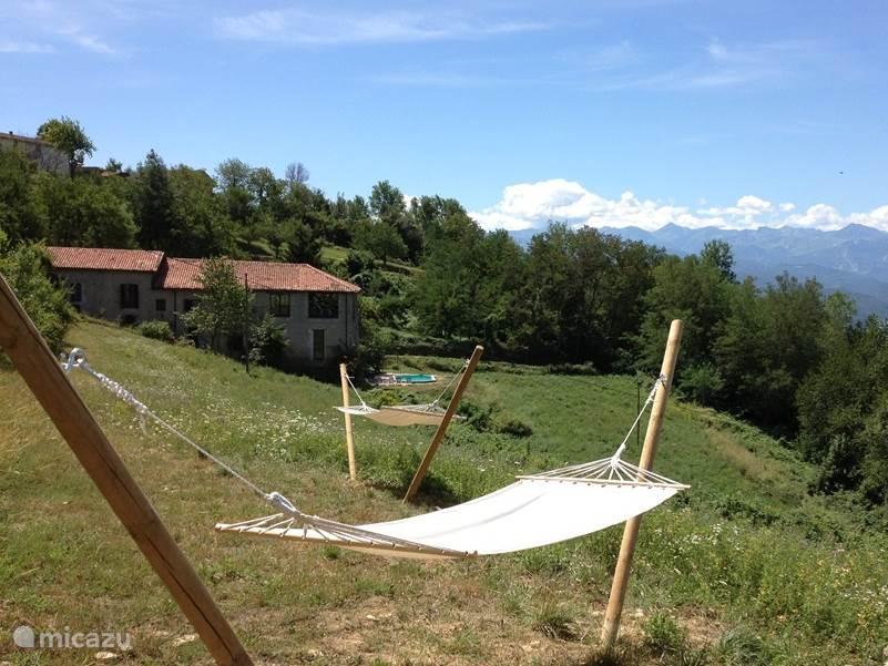 Vanuit de hangmat heb je prachtig uitzicht op de achterkant van het huis en de omgeving. Bij helder weer is de Monviso te zien.