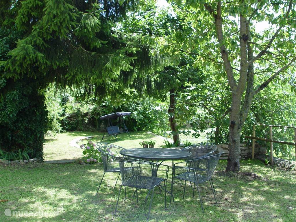 De tuin met daarachter de oude moestuin met kakiboom, pruimenboom vijgenbomen en druiven.