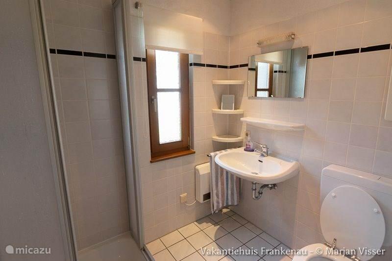Een ruime badkamer met toilet