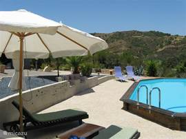 Aan het zwembad, met uitzicht over de omringende heuvels, is het heerlijk toeven onder een parasol, en natuurlijk ook in de zon.