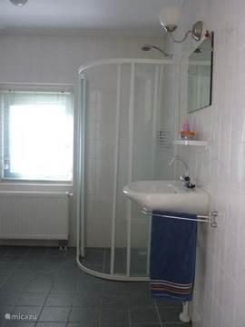 De ruime badkamer met wastafel en douche. Niet op de foto maar wel aanwezig een wasmachine en droger. het toilet zit er naast, het is gescheiden van de badkamer.