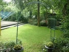 Een doorkijkje in de tuin. Het open bladerdak van de eiken geeft in de zomer mooie schaduwplekken maar voor de zonaanbidder is er ook ruimte om heerlijk te zonnen.