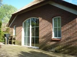 Het terras loopt door aan de achterzijde van het huisje, diezelfde zonnestralen zetten tegen het eind van de middag ook de achterzijde in het zonnelicht.
