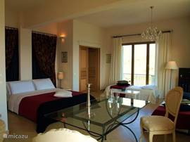Slaapkamer(37m2),sfeervol ingericht, rondom openslaande deuren naar de terrassen.