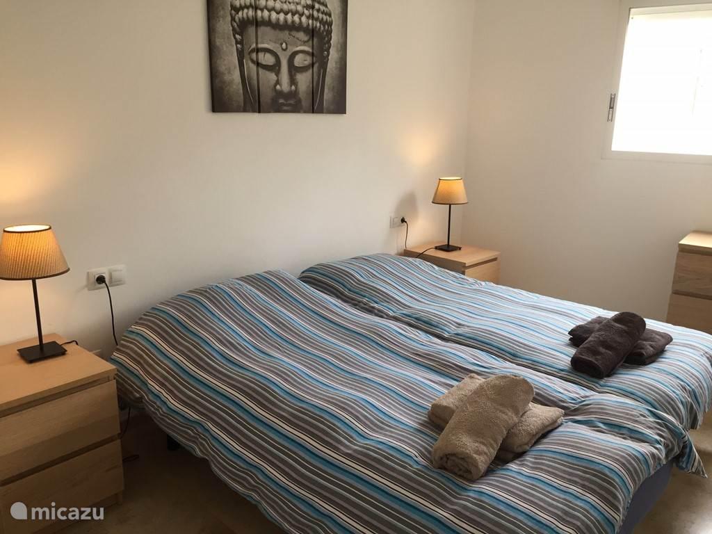 Slaapkamer 1 met twee eenpersoonsbedden die aan elkaar vast staan. Bedlampjes, grote inbouwkasten en ladekast aanwezig