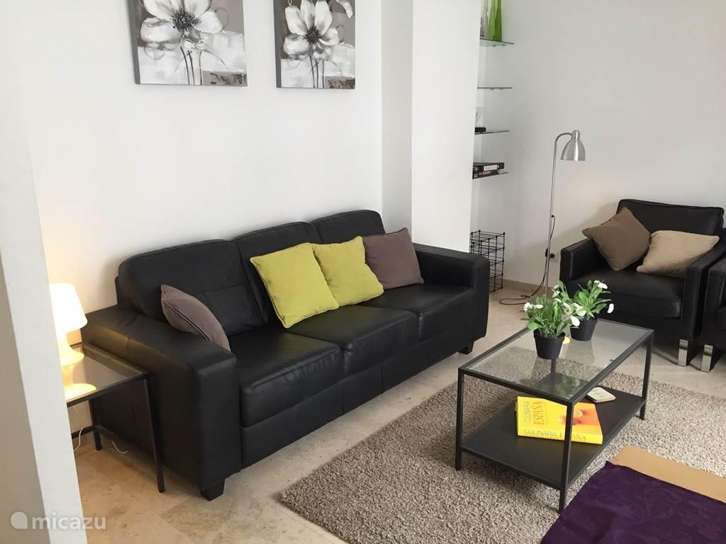 Gezellige woonkamer voorzien van goede bank en twee fauteuils.