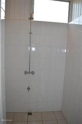 badkamer met douche, wastafel en apart toilet.