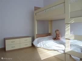 De slaapkamer met het stapelbed. Links staat nog een ruime klerenkast en aan de voorkant een buro. De ramen zijn voorzien van luxaflex, waardoor het binnen redelijk koel blijft.
