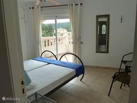 Slaapkamer 4 op de 1e verdieping. Alle 3 de slaapkamers hebben airco, kluisje en openslaande deuren naar het riante balcon van 10x3m.