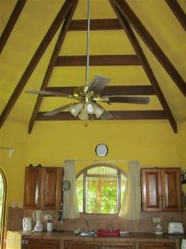 living room with kitchen area has a high ceiling with a fan attached to it. The same ventilators can be found in the bedrooms.