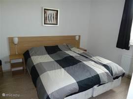 Ruime slaapkamer op begane grond met twee éénpersoonsbedden met aangrenzend een luxe badkamer met douche, wastafel  en een apart toilet
