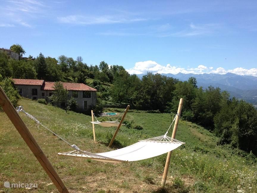 Vanuit de hangmat heb je prachtig zicht op de achterkant van het huis en de omgeving. Bij helder weer is de Monviso te zien.