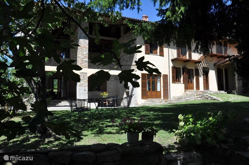 Het huis vanaf de binnentuin. De tuin heeft diverse zitjes en twee, in Italië traditionele grote eettafels waar je makkelijk met zijn 12-en omheen kan zitten.