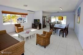 In de luchtige huiskamer vindt u o.a. de caribische zithoek en de grote eetkamertafel met 6 stoelen. Ook is er een hoog/laag kinderstoeltje aanwezig.