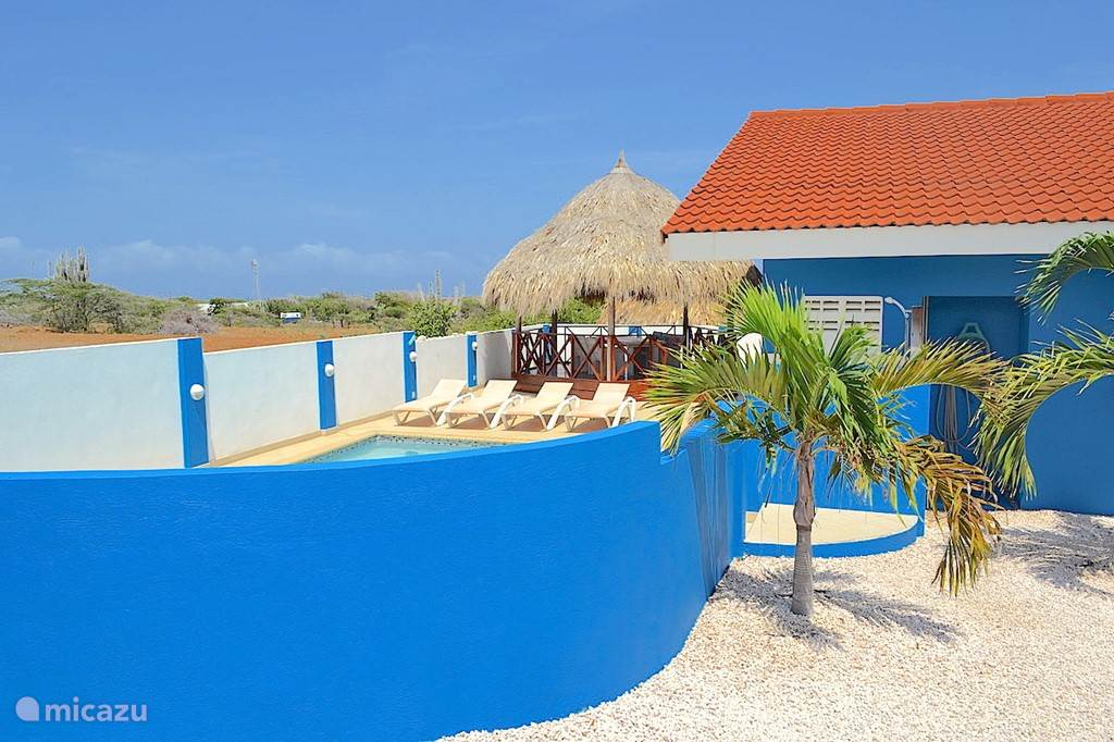 Villa Blou Curacao, de ronde muur onttrekt het zwembad uit het zicht vanaf de straat.