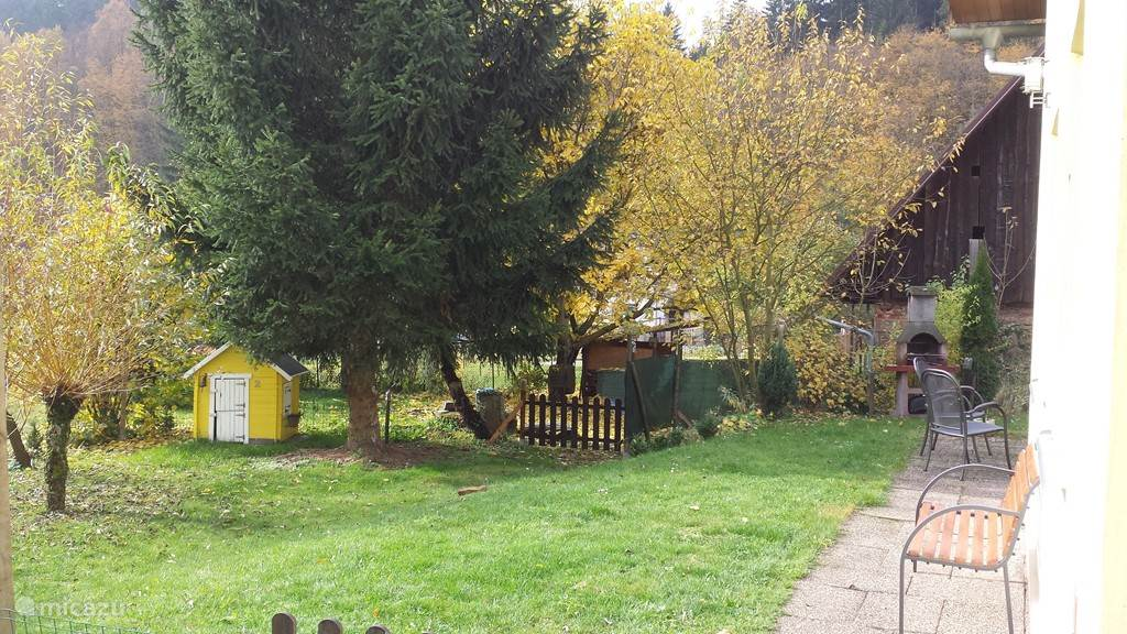 The garden surrounds the house. In this photo, the bbq place and to see the children's playhouse.