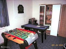 recreation room with table football, pool table, dart board, blackboard and cupboard with games and books