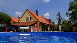 Uitzicht op vakantieboerderij en  zwembad in de  voortuin vanaf het buitenterras