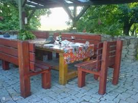 De robuuste eettafel op het buitenterras biedt plaats aan 12 personen. Hier bevindt zich ook een buitenkeuken met grill.