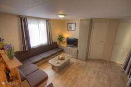 De zeer grote woonkamer met hoekbank welke plek biedt aan 6 personen. Daarnaast een salontafel, tv meubel en grote kast. Op het meubel staat er een LCD tv welke op de kabel aangesloten is en is er een DVD-speler aangesloten.