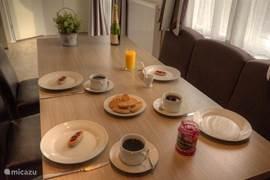 De riante eethoek welke bestaat uit een zeer grote tafel met vast bank voor drie personen. Aan de andere kant van de tafel drie losse stoelen van leer.